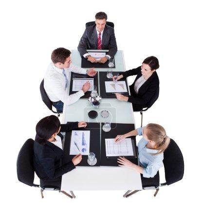 Photo pour Vue d'angle élevé de gens d'affaires discuter sur des graphiques à la table de conférence sur fond blanc - image libre de droit