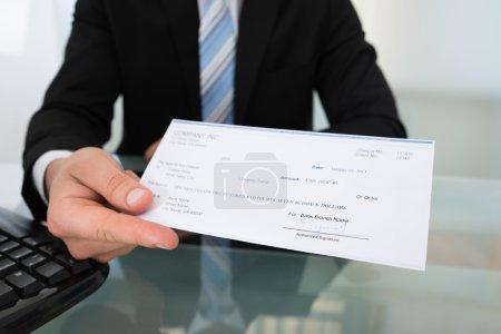 Photo pour Midsection de l'homme d'affaires donnant chèque au bureau - image libre de droit
