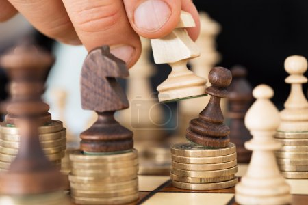 Photo pour Closeup of hand playing chess stacked on coins - image libre de droit