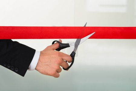 Businessman Cutting Red Ribbon