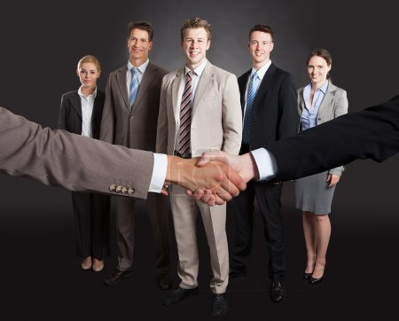 Photo for Cropped image of businessmen shaking hands with confident team standing behind over gray background - Royalty Free Image