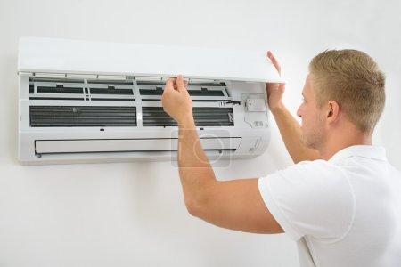 Photo pour Portrait d'un jeune homme ajustant le système de climatisation - image libre de droit