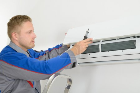 Foto de Young Man Repairing Air Conditioner Standing On Stepladder - Imagen libre de derechos