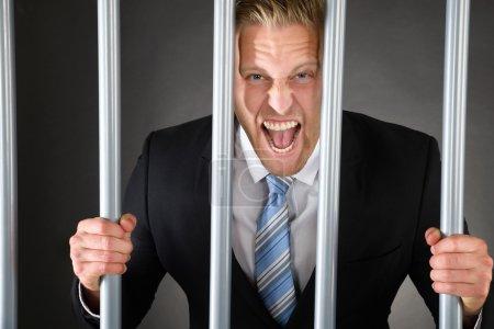Aggressive Businessman Behind Bars