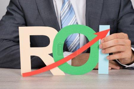 Photo pour Milieu de l'homme d'affaires détenant ROI (retour sur investissement) avec flèche vers le haut à la table - image libre de droit