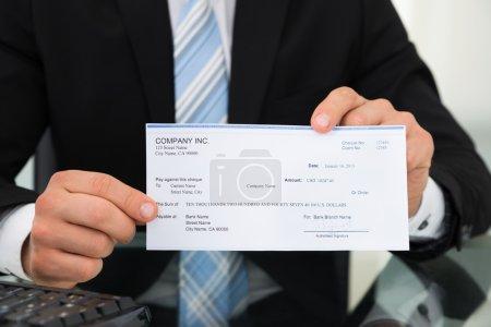 Photo pour Milieu de l'homme d'affaires montrant le chèque au bureau - image libre de droit