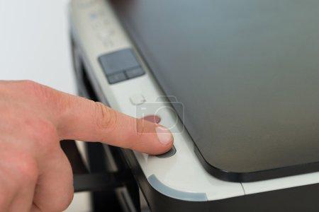 Businessman Pressing Button Of Photocopy Machine