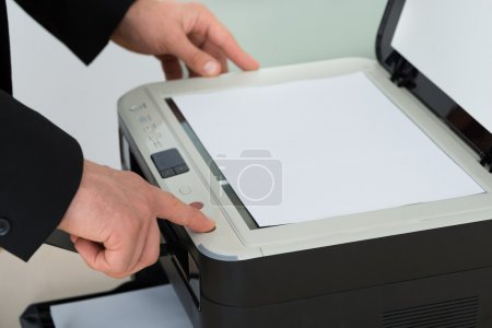 Businessman Pressing Button Of Photocopy Machine