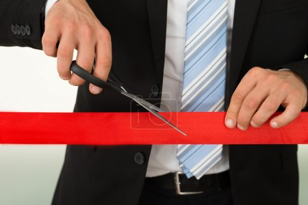 Photo for Midsection of businessman cutting red ribbon with scissors over white background - Royalty Free Image