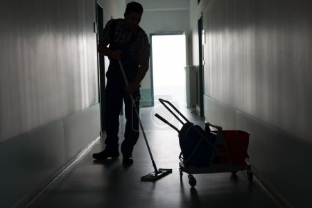 Male Worker Cleaning Office Corridor