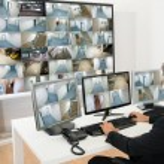 Man In Control Room Monitoring Multiple Cctv Foota...