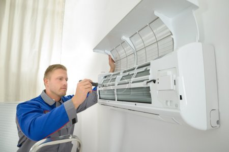 Photo pour Young Man Repairing Air Conditioner Standing On Stepladder - image libre de droit