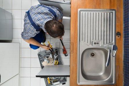 Plumber Examining Kitchen Sink