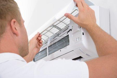 Photo pour Fermez-vous vers le haut de la verticale de jeune homme ajustant le système de climatisation - image libre de droit