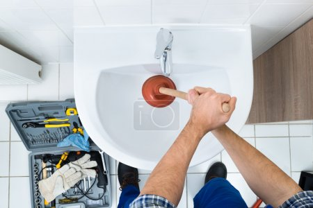 Male Plumber Using Plunger