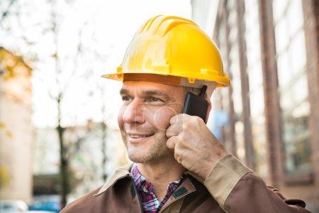 Photo for Happy Builder Wearing Hardhat Talking On Walkie Talkie - Royalty Free Image