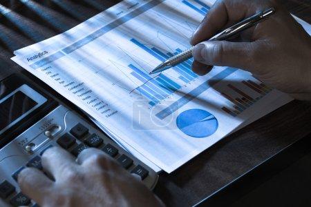 Photo pour Gros plan d'une personne à l'aide de la calculatrice et l'analyse graphique - image libre de droit