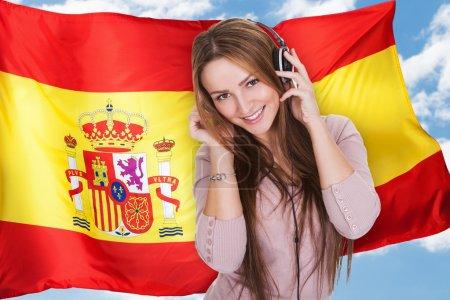 Photo pour Femme écoutant espagnol Apprendre Livre audio sur écouteurs devant drapeau espagnol - image libre de droit