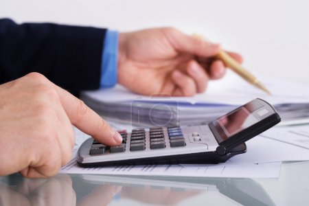 Photo for Close-up Of A Businessman's Hand Using Calculator at desk - Royalty Free Image