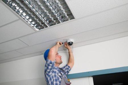 Photo pour Homme technicien réglage caméra de sécurité Cctv sur plafond - image libre de droit