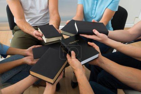 Photo pour Gros plan de personnes assises ensemble tenant la Sainte Bible - image libre de droit