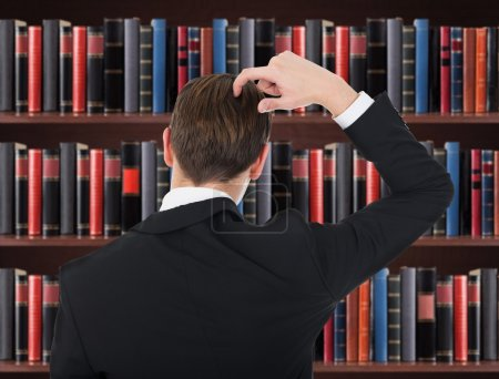 Photo pour Un homme en costume se gratte la tête dans la salle d'audience - image libre de droit