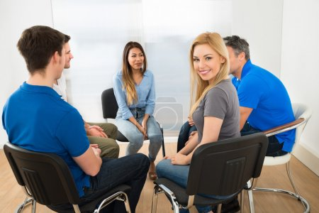 Photo pour Portrait de heureuse belle jeune femme assise avec ses amis - image libre de droit
