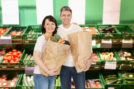 Photo for Happy Mature Couple Holding A Groceries Bags In Supermarket - Royalty Free Image