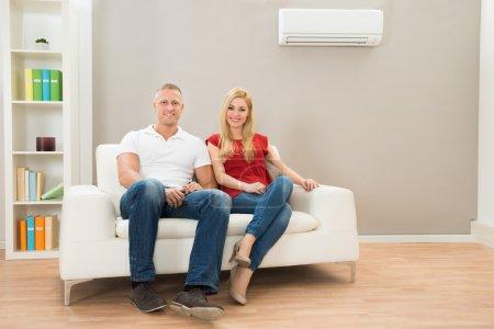 Photo pour Portrait de jeune couple heureux assis sur le canapé - image libre de droit