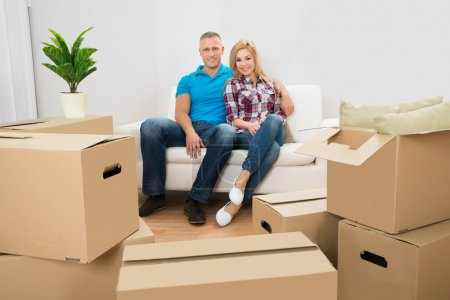 Photo for Couple Sitting On Couch In New Home With Cardboard Boxes - Royalty Free Image