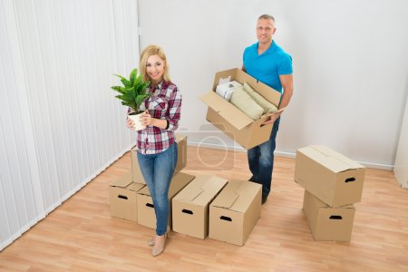 Photo for Portrait Of Happy Young Couple Moving Boxes In New Home - Royalty Free Image