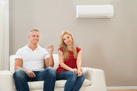 Photo pour Jeune couple heureux assis sur un canapé blanc en utilisant la climatisation - image libre de droit