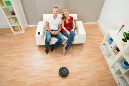 Photo for Young Couple Using Remote Control Toward Robotic Vacuum Cleaner - Royalty Free Image