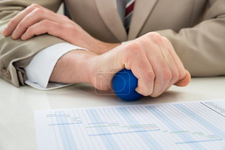 Photo for Close-up Of Businessperson Hand Squeezing Stressball In Hand - Royalty Free Image