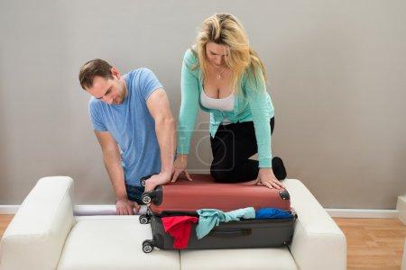Photo pour Couple ensemble essayant de fermer leurs bagages - image libre de droit