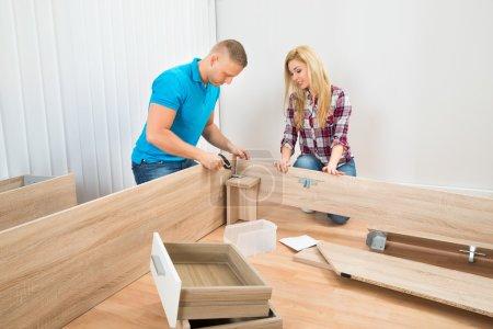 Photo pour Jeune Couple montage meuble dans Maison Neuve - image libre de droit
