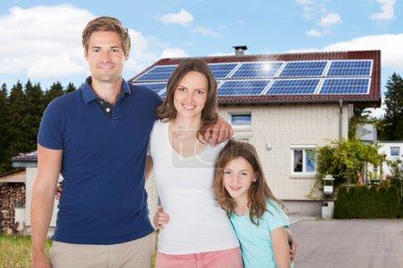 Foto de Familia de pie en la casa delantera con panel solar en el techo - Imagen libre de derechos