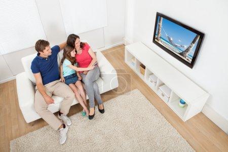 Photo pour Vue d'angle élevé de famille regardant la tv ensemble tout en se relaxant sur le sofa à la maison - image libre de droit