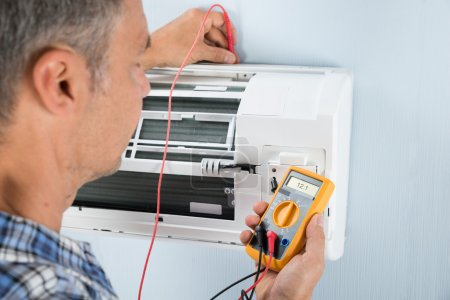 Photo for Portrait Of A Mid-adult Male Technician Testing Air Conditioner With Digital Multimeter - Royalty Free Image