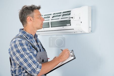 Technician Looking At Air Conditioner