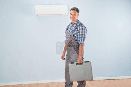 Photo for Photo Of Air Conditioner Repairman With Toolkit - Royalty Free Image