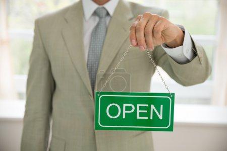 Photo pour Gros plan d'un homme d'affaires tenant une pancarte ouverte - image libre de droit