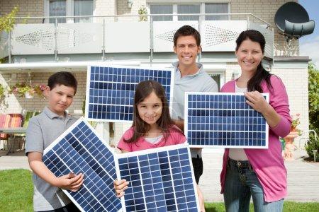 Foto de Foto de familia feliz llevando paneles solares - Imagen libre de derechos