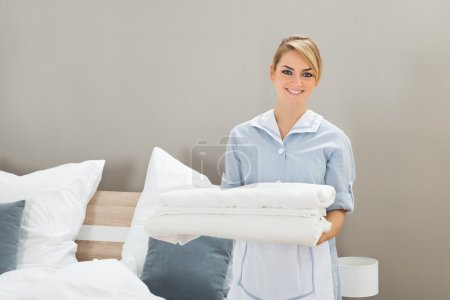 Housekeeper Holding Stack Of Sheets