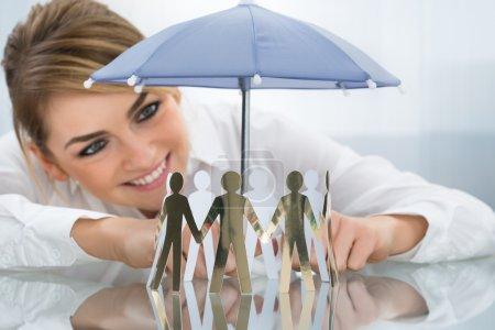 Photo pour Jeune femme d'affaires heureuse protégeant des figures découpées avec petit parapluie - image libre de droit