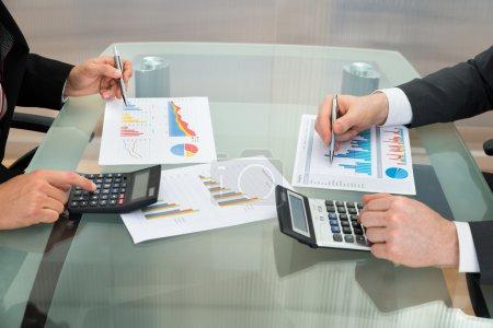 Photo pour Gros plan de deux hommes d'affaires analysant le graphique à l'aide d'une calculatrice sur bureau - image libre de droit