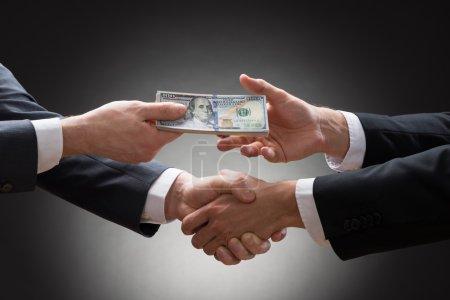 Businessmen Shaking Hands And Receiving Money