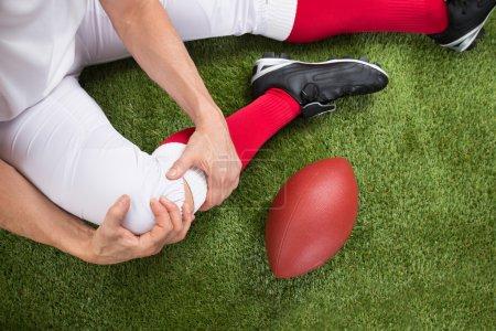 Foto de Primer plano de un jugador de fútbol americano con lesión en la pierna en el campo - Imagen libre de derechos