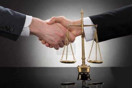 Photo pour Gros plan de deux hommes d'affaires, se serrant la main devant les échelles - image libre de droit