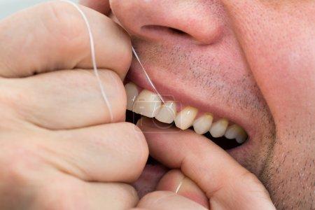 Photo pour Gros plan d'un homme portant la soie dentaire - image libre de droit